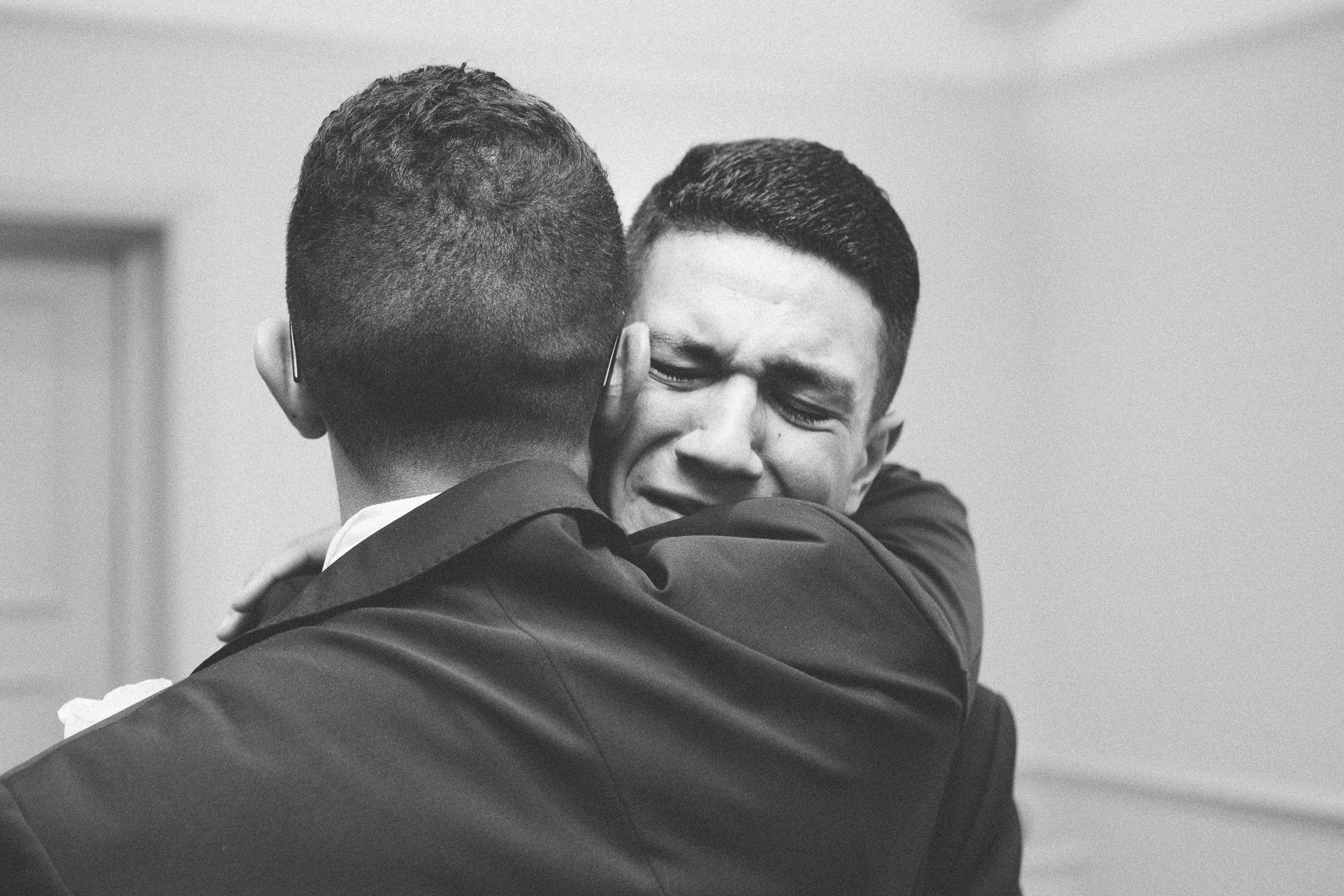 Groom hugs his very emotional brother after getting married. Photography by thatthingyoupluck.