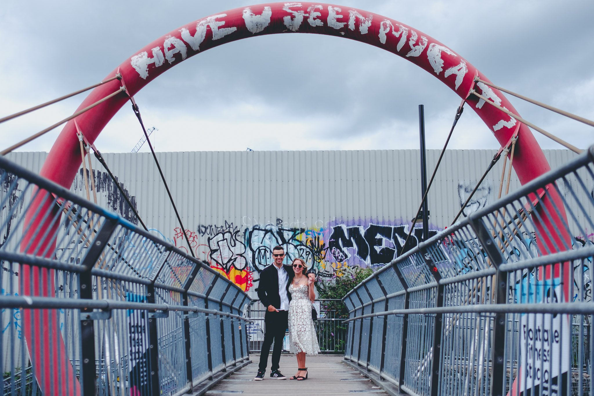 Engagement portrait of couple on a bridge