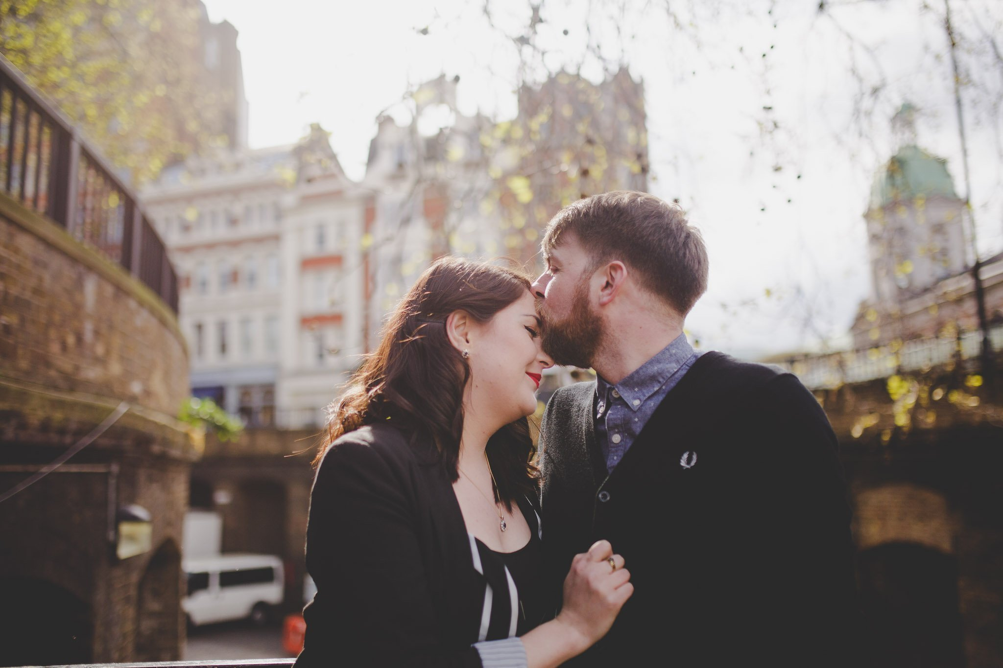 Couple hug and kiss in a street in Clerkenwell London for an engagement shoot. Photography by thatthingyoupluck.