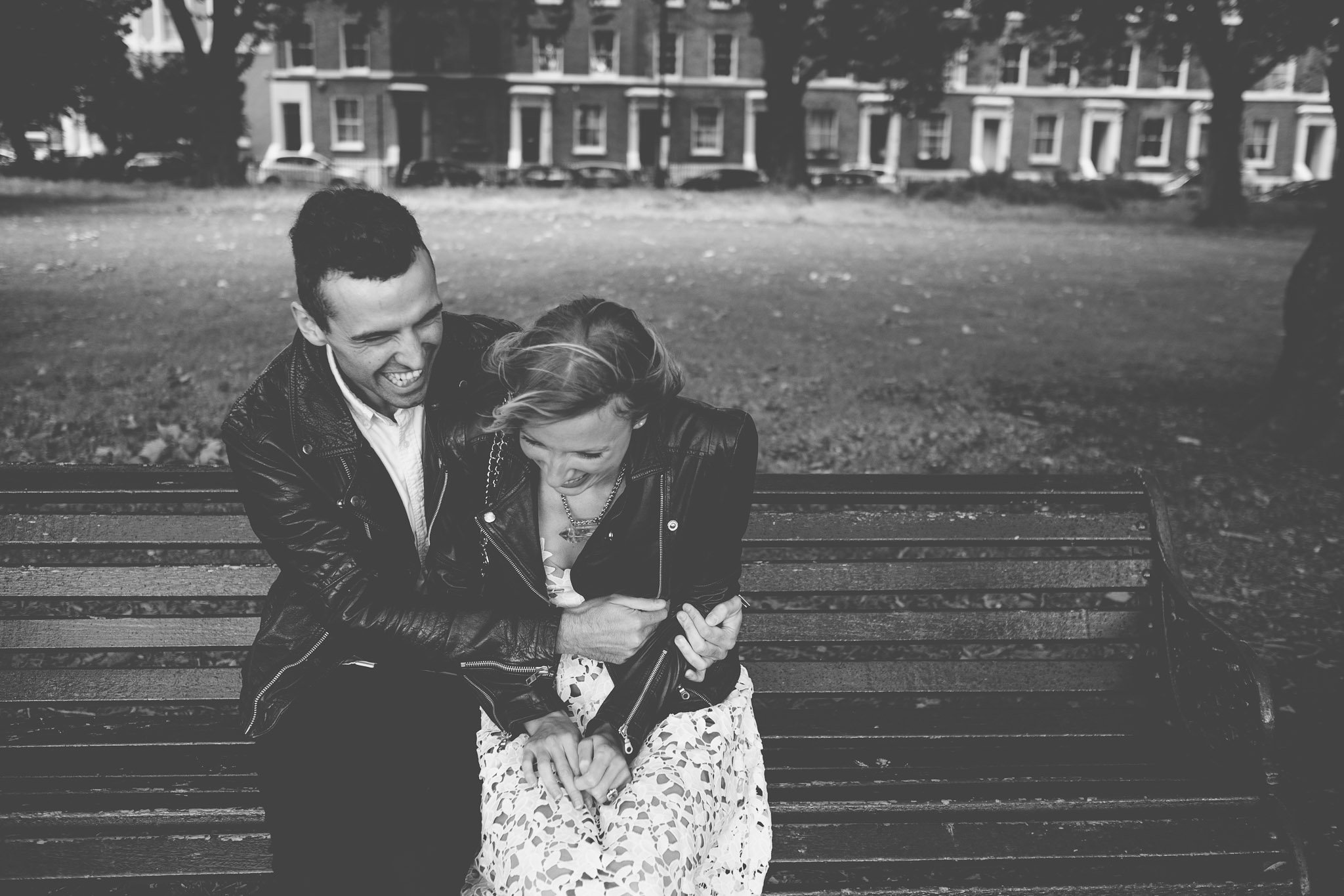 A young couple with matching leather jackets on a park bench laughing on an engagement shoot in Victoria Park. Photography by thatthingyoupluck.