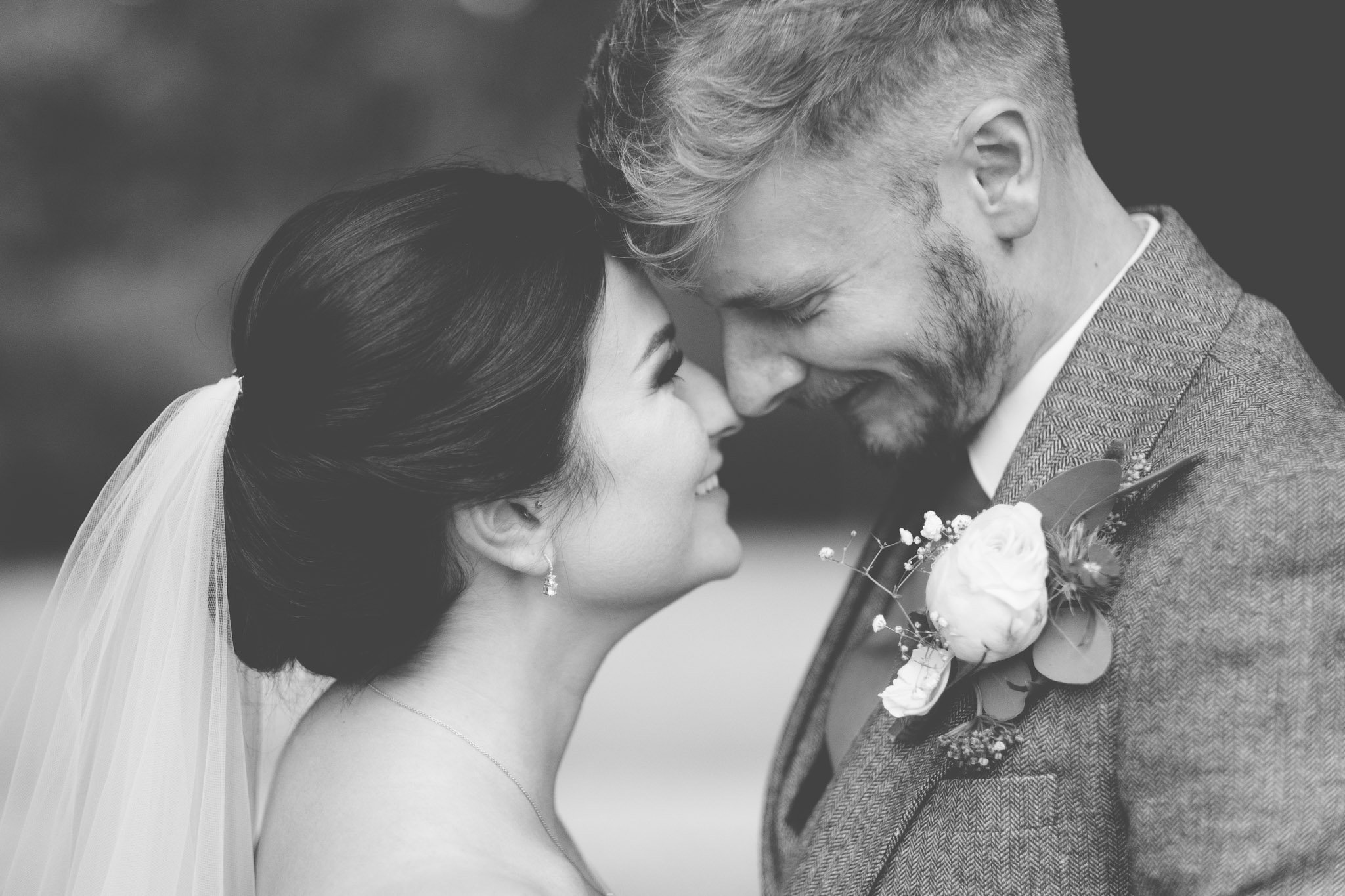 Close up of a newly married couple facing each other with their foreheads and noses touching. Photography by thatthingyoupluck.