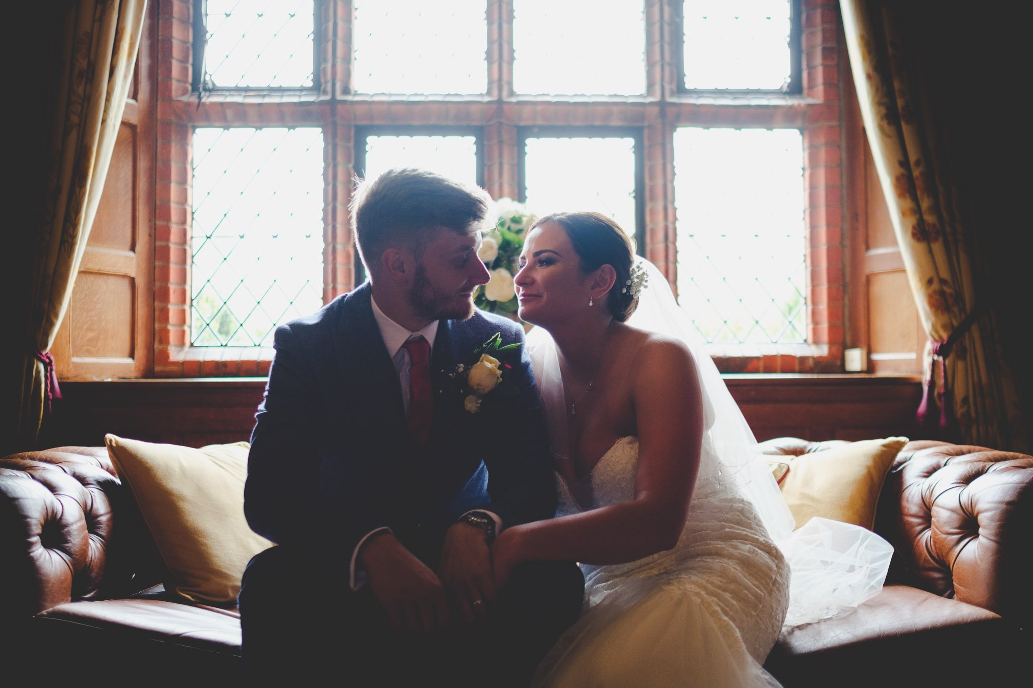 Just married bride & groom cuddle on a Chesterfield sofa in front of a window at Leez Priory Chelmsford. Photography by thatthingyoupluck