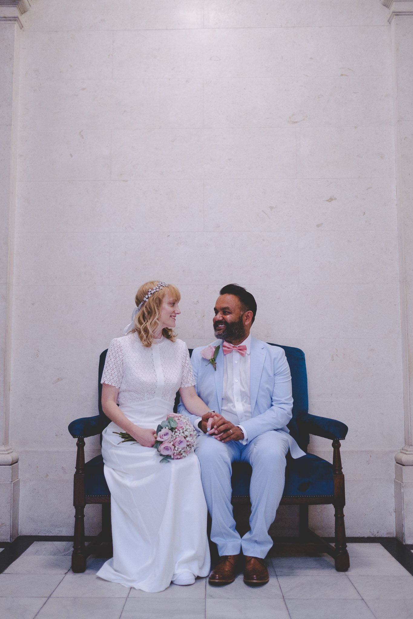 Newly married couple sitting holding hands at Marylebone Town Hall Wedding London. Photography by thatthingyoupluck.