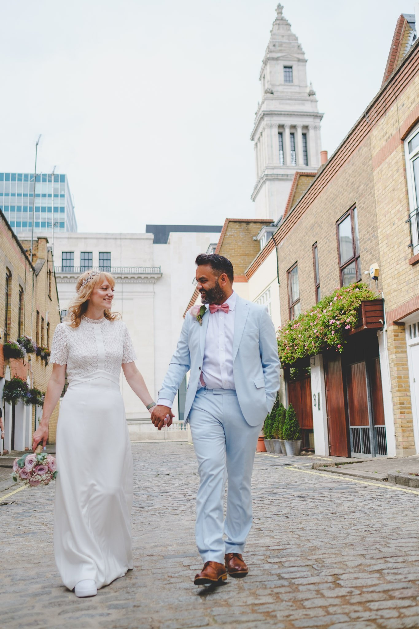 Bride and groom stand facing the front holding hands in front of an archway by creative london wedding photographer thatthingyoupluck